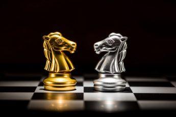 ajedrez-caballero-oro-frente-ajedrez-caballero-plata-tablero-ajedrez_35570-76